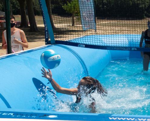 Jugadora de watervoley se tira a por un balón en una piscina deportiva profesional de water sport pools®